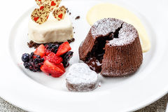 Chocolate fondant lava cake with ice cream strawberries and berries. On white plate on marble serface stock photo