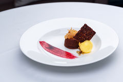 Chocolate fondant with lemon ice cream and raspberry sauce. On white plate on white tablecloth royalty free stock photos