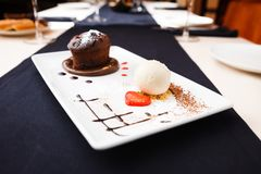 Chocolate fondant on a plate. Chocolate fondant with vanilla ice cream and raspberry sauce stock photos