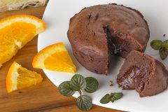 Chocolate fondant on a plate. Hot chocolate fondant on a plate with mint and oranges stock photography