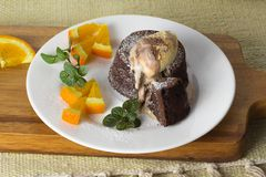Chocolate fondant on a plate. Hot chocolate fondant on a plate with mint, oranges and ice cream stock photo
