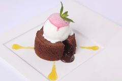 Chocolate fondant with sauce and mint. On plate royalty free stock photography