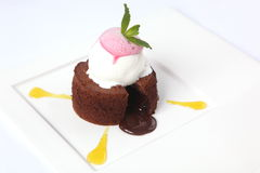 Chocolate fondant with sauce and mint. On plate stock image