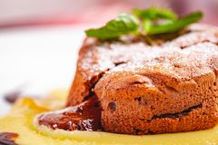 Chocolate fondant served with custard cream on white plate. Lava cake recipe. Close up royalty free stock photos