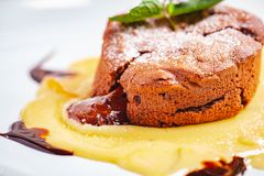 Chocolate fondant served with custard cream on white plate. Lava cake recipe. Close up stock images