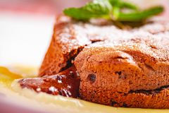Chocolate fondant served with custard cream on white plate. Lava cake recipe. Close up royalty free stock images
