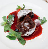 Chocolate fondant with sweet berry sauce. Chocolate fondant with berry sauce on plate royalty free stock images
