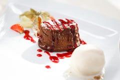 Chocolate fondant with ice cream. Chocolate fondant with vanilla ice cream and raspberry sauce royalty free stock photos