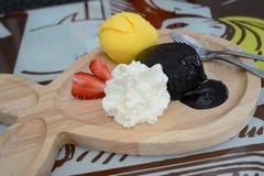 Chocolate fondant with vanilla ice cream. On wooden plate stock photos