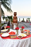 Chocolate Fondue Fountain - Flowers / Fruits. Chocolate Fondue Fountain at sunset on he beach with fruits and flowers. Roses, Strawberries, Pineapple slices Stock Photo