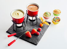 Chocolate fondue with fruit, sprinkles and nuts. Chocolate fondue with fresh fruit including strawberries, gooseberry and raspberries with side dishes of Stock Image