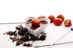 Chocolate fondue melted with fresh strawberries and dark chocola. Chocolate fondue melted with fresh strawberries and milk chocolate pieces Royalty Free Stock Photo