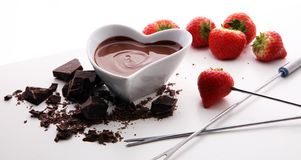 Chocolate fondue melted with fresh strawberries and dark chocola. Chocolate fondue melted with fresh strawberries and milk chocolate pieces Royalty Free Stock Photography