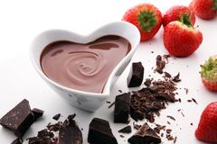 Chocolate fondue melted with fresh strawberries and dark chocola. Chocolate fondue melted with fresh strawberries and milk chocolate pieces Royalty Free Stock Photos