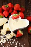 Chocolate fondue melted with fresh strawberries and white chocol. Ate pieces Royalty Free Stock Image