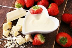 Chocolate fondue melted with fresh strawberries and white chocol. Ate pieces Royalty Free Stock Images