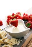 Chocolate fondue melted with fresh strawberries and white chocol. Ate pieces Royalty Free Stock Photos