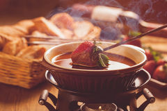 Chocolate fondue. With oven on wooden table stock images