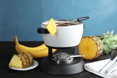 Chocolate fondue in pot and ripe fruits. On wooden table royalty free stock images