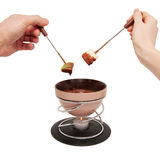 Chocolate fondue. Two hands, male and female, with fruit. Royalty Free Stock Image