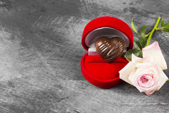 Chocolate in the form of heart in a red case for a ring, a pink. Rose on a dark background. Concept love for chocolate. Copy space. Food background Royalty Free Stock Image