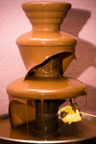 Chocolate fountain. Hot chocolate pouring down from fountain Stock Photo
