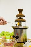 Chocolate fountain. With hand and fork Royalty Free Stock Image