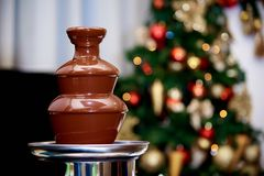 Chocolate fountain on a blurred background with multi-colored bokeh. royalty free stock photography