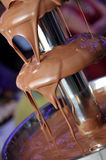 Chocolate fountain. Hot molten chocolate flowing down. Dripping chocolate Stock Photo