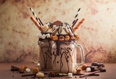 Chocolate freak or crazy shake. Chocolate  milkshake with ice cream and with whipped cream, marshmallow, sweet popcorn, cookies, waffles, served in glass mason Stock Images