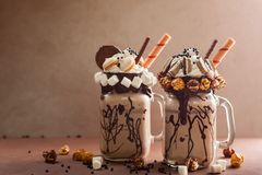 Chocolate freak or crazy shake. Chocolate  milkshake with ice cream and with whipped cream, marshmallow, sweet popcorn, cookies, waffles, served in glass mason Stock Image