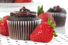 Chocolate Frosted Cupcake and Strawberry. A chocolate cupcake with chocolate frosting served with fresh ripe strawberries Stock Image