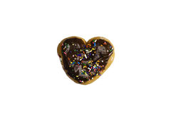 Chocolate frosted donut. A chocolate frosted heart shaped donut with sprinkles isolated on a white background Stock Image