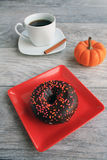 Chocolate frosted dough nut with mug of pumpkin spice coffee Royalty Free Stock Photos