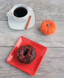 Chocolate frosted  with sprinkles dough nut with mug of pumpkin spice coffee Royalty Free Stock Photo