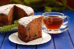 Chocolate fruit cake with black tea and green fur tree branch on Royalty Free Stock Image