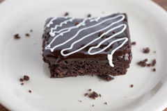 Chocolate Fudge Brownies with Chocolate Ganache and White Chocol. Chocolate Fudge Brownie on a white plate with a drizzle of white chocolate over the top Royalty Free Stock Photo