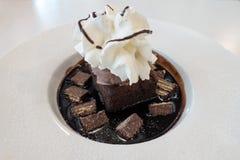 Chocolate fudge cake and ice cream on chocolate sauce Royalty Free Stock Image