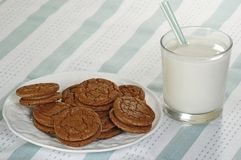 Chocolate fudge cookies. Plate of chocolate fudge cookies and milk on a green tablecloth Royalty Free Stock Images