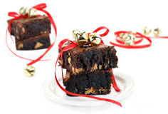 Chocolate Fudge Peanut Butter Brownies. Chocolate fudge and peanut butter brownies on a white background wrapped in red ribbons and golden bells for Stock Image