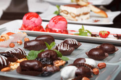 Chocolate gathering. Chocolates, nuts, strawberry sorbet, fresh mint Royalty Free Stock Photography