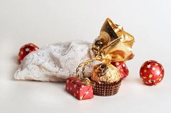 Chocolate gift. Chocolate candy in red metallic paper with stars lay near white & golden bag for gifts on white background Stock Photos