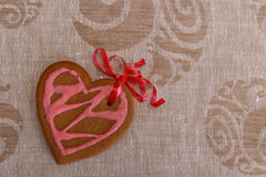 Chocolate gingerbread cookies heart shaped with red and pink icing and red ribbon next colorful fabric Royalty Free Stock Photo