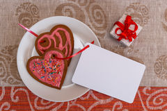 Chocolate gingerbread cookies heart shaped with red and pink icing and red ribbon next on colorful fabric Stock Image