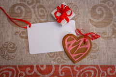 Chocolate gingerbread cookies heart shaped with red and pink icing and red ribbon next on colorful fabric Royalty Free Stock Photography
