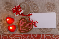 Chocolate gingerbread cookies heart shaped with red and pink icing and red ribbon next on colorful fabric Stock Photography