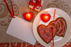 Chocolate gingerbread cookies heart shaped with red and pink icing and red ribbon next on colorful fabric Stock Images