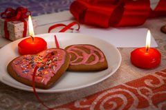 Chocolate gingerbread cookies heart shaped with red and pink icing and red ribbon next on colorful fabric Royalty Free Stock Images