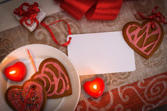 Chocolate gingerbread cookies heart shaped with red and pink icing and red ribbon next on colorful fabric Stock Photos