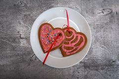 Chocolate gingerbread cookies heart shaped with red and pink icing on white plate Royalty Free Stock Photos